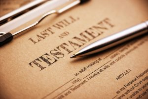 a last will and testament on a clip board. A form is printed on a light brown mulberry paper and waiting to be filled and signed by testator / testatrix.